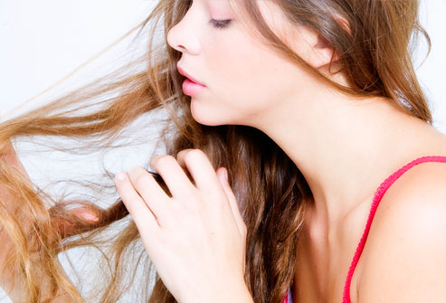 Young woman running fingers through hair